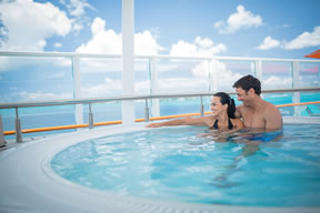 Couple relaxing in hot tub on the NCL Breakaway